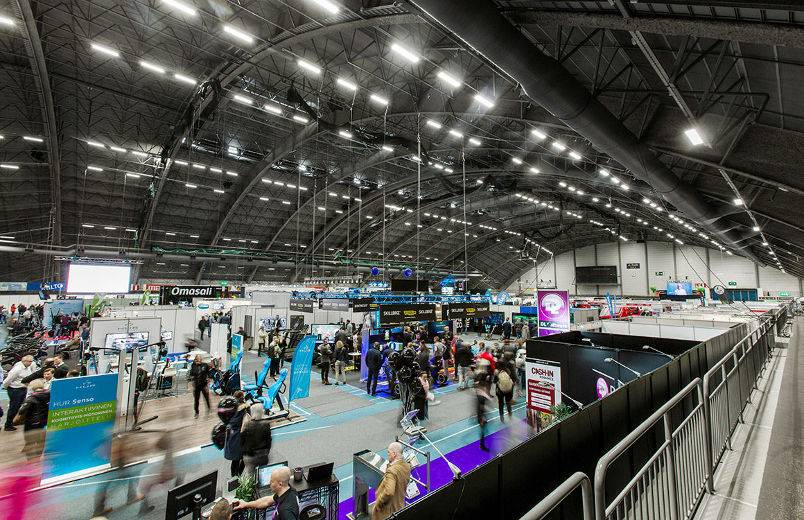 During trade fairs at Tampere Exhibition and Sports Centre, the lighting levels of the ceiling luminaires are lowered to bring out the stand lighting designs.