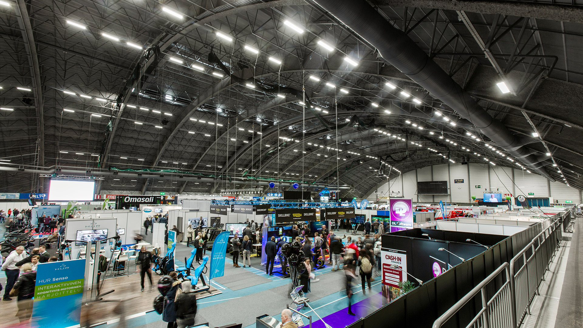 During a fair at Tampere Exhibition and Sports Centre, the control system is used to reduce the lighting levels of the hall to bring out the lighting design of the stands.